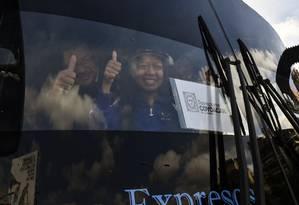 Opositores acenam de ônibus que viajam de Caracas à fronteira venezuelana com a Colômbia Foto: YURI CORTEZ / AFP
