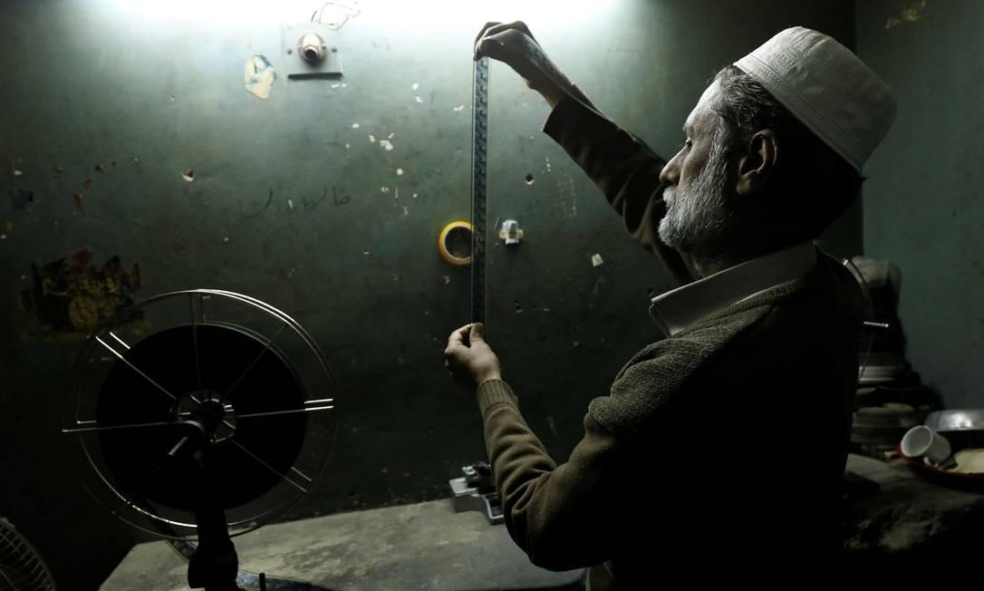 Um trabalhador verifica uma tira de filme em uma casa de cinema em Peshawar, no Paquistão Foto: FAYAZ AZIZ / REUTERS