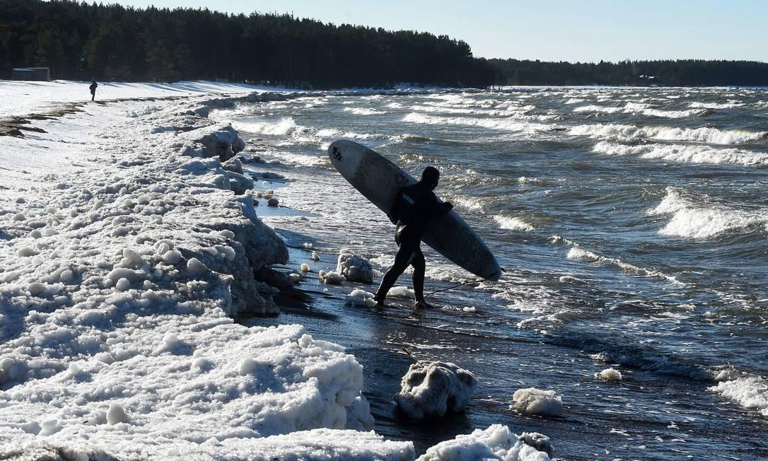 Surfista entra nas águas geladas do Golfo da Finlândia, em uma aldeia nos arredores de São Petersburgo Foto: OLGA MALTSEVA / AFP