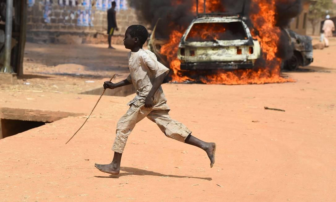Um menino corre quando carros são incendiados após confrontos em Kano, na Nigéria, às vésperas de eleição Foto: PIUS UTOMI EKPEI / AFP