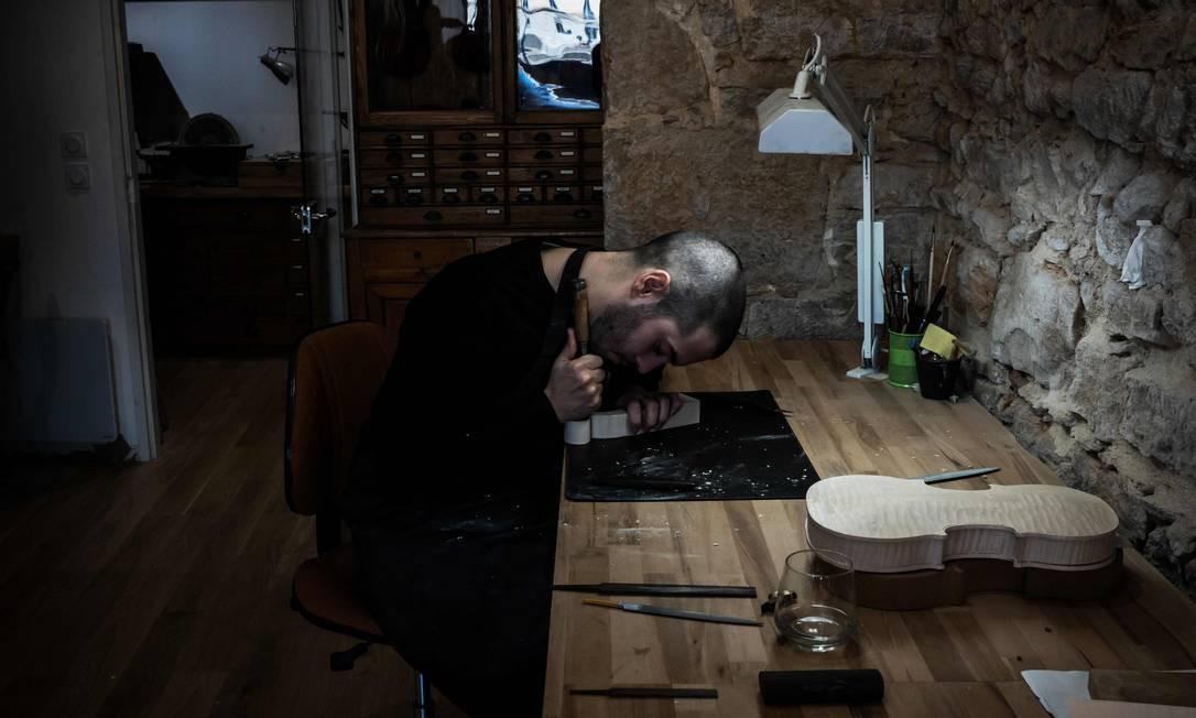 Um fabricante suíço de violinos trabalha em sua oficina Foto: JEFF PACHOUD / AFP