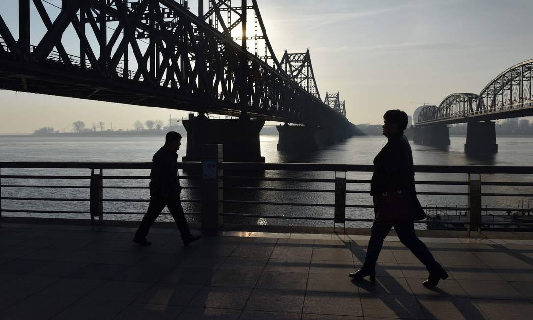 As pessoas caminham abaixo da Ponte da Amizade, que atravessa o rio Yalu, entre a China e a Coréia do Norte, na cidade chinesa de Dandong Foto: GREG BAKER / AFP