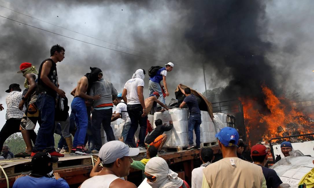 Voluntários tentam salvar produtos em caminhões de ajuda internacional incendiado por militares pró-Maduro em Cúcuta, na fronteira entre Colômbia e Venezuela Foto: MARCO BELLO / REUTERS