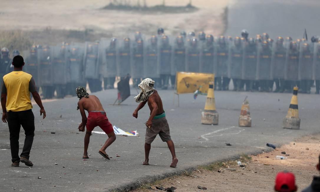Venezuelanos do lado brasileiro da fronteira lançam pedras contra militares da Guarda Nacional da Venezuela, do outro lado Foto: RICARDO MORAES / REUTERS