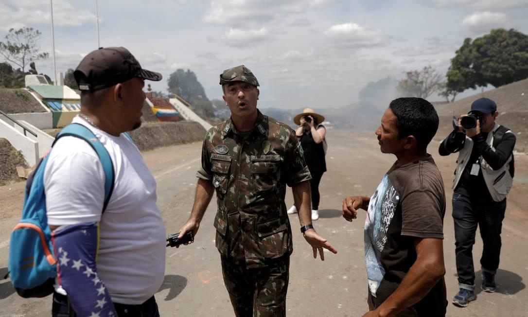 O coronel brasileiro George Feres Canaã pede aos manifestantes que parem de atirar objetos nos militares venezuelanos Foto: RICARDO MORAES / REUTERS