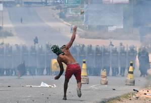 Manifestante atira pedras contra membros da Guarda Nacional Bolivariana da Venezuela na fronteira com o Brasil, em Pacaraima Foto: NELSON ALMEIDA / AFP