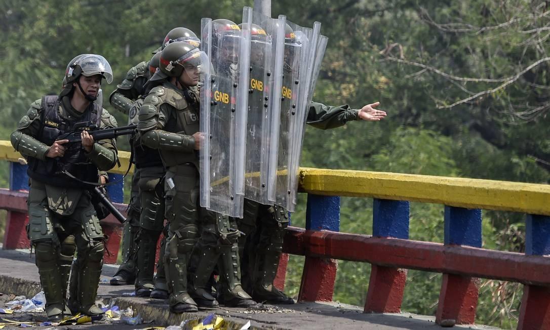 Integrantes da Guarda Nacional Bolivariana da Venezuela se protegem de manifestantes em Urena, Venezuela, fronteira com a Colômbia e Foto: LUIS ROBAYO / AFP