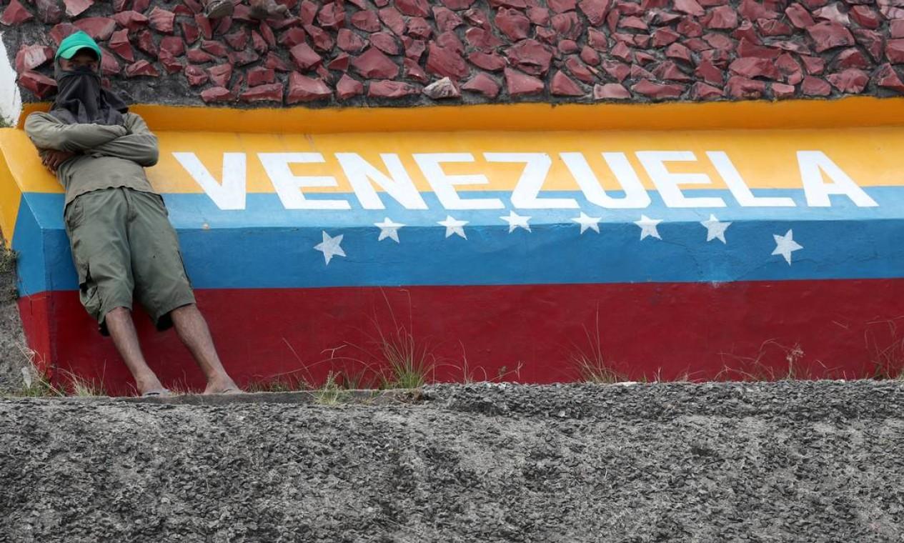 Manifestantes contra governo de Nicolás Maduro se senta sobre a divisa entre Brasil e Venezuela; em dois dias, seis pessoas morreram em confrontos com militares venezuelanos Foto: RICARDO MORAES / REUTERS