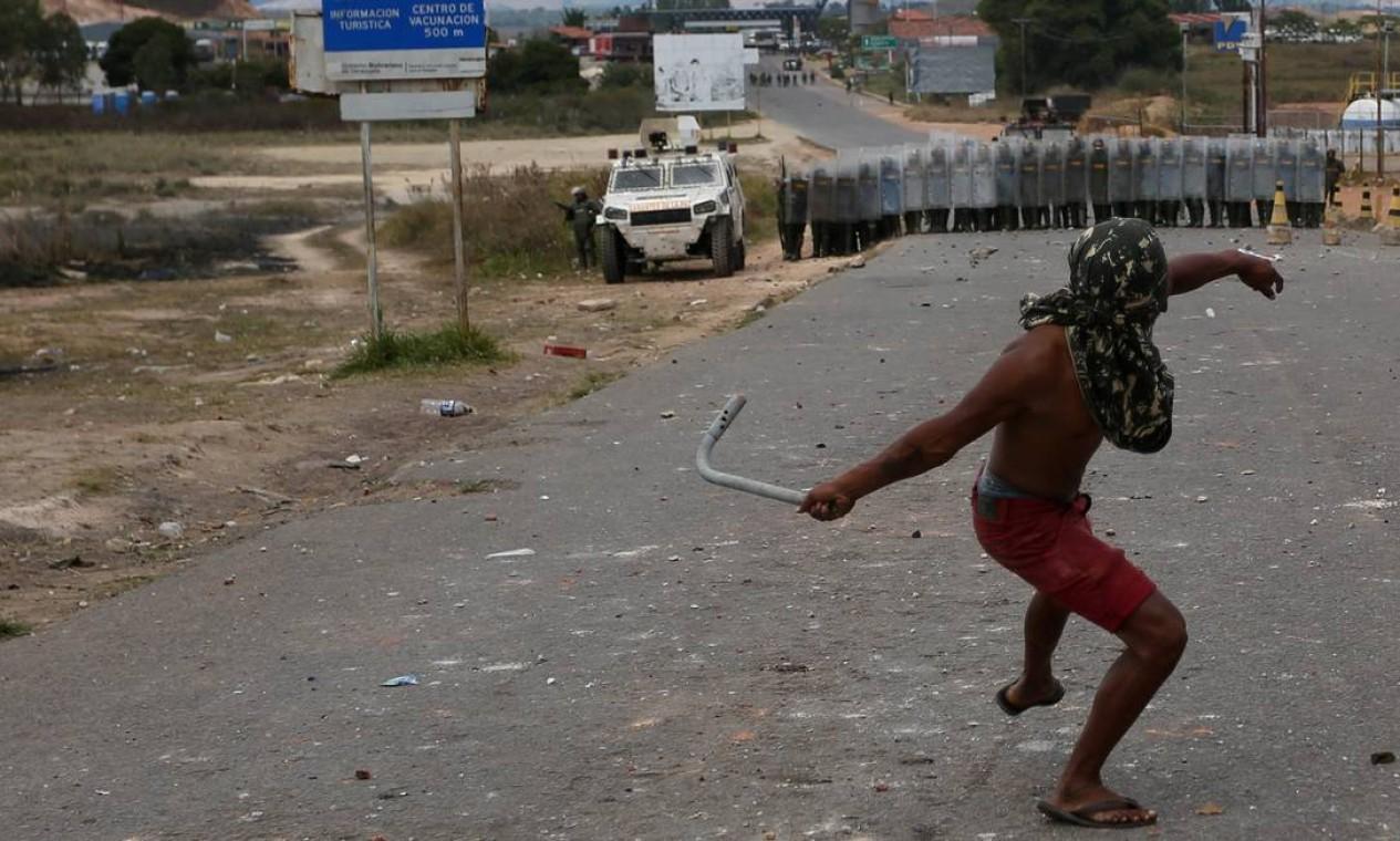 Homem lança objeto de metal contra agentes venezuelanos em Pacaraima, no estado brasileiro de Roraima; tentativas dea oposição venezuelana de levar carregamentos de ajuda humanitária do Brasil à Venezuela falharam nos primeiros dois dias Foto: BRUNO KELLY / REUTERS