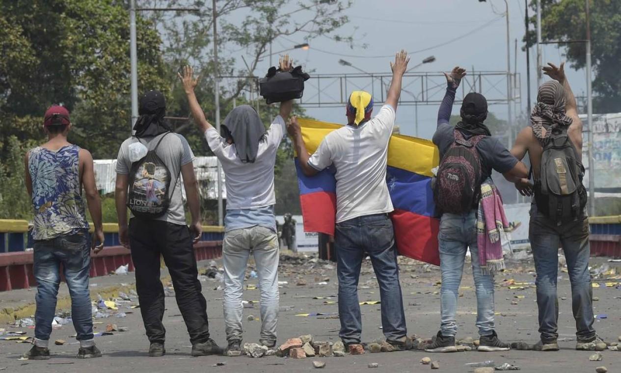 Pequeno grupo de manifestantes em provocações a agentes militares venezuelanos na ponte internacional Francisco de Paula Santander , uma das que conectam Venezuela e Colômbia Foto: RAUL ARBOLEDA / AFP