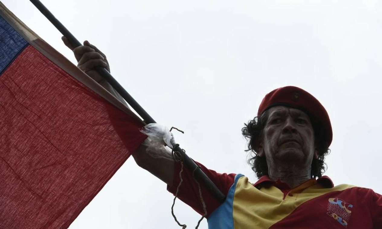 Apoiador do presidente Nicolás Maduro balança bandeira durante discurso de representantes do governo de Caracas no lado venezuelano da fronteira com a Colômbia; lá, mais de cem militares já desertaram Foto: FEDERICO PARRA / AFP