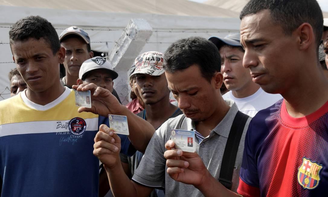 Membros da Guarda Nacional Bolivariana (GNB) mostram cartões de identidade militares após desertarem na fronteira com o Brasil Foto: RICARDO MORAES / REUTERS