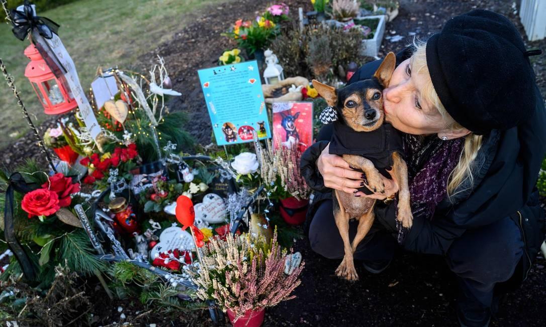 Karla Lemke beija seu pinscher, de 15 anos, enquanto visita o túmulo de seu outro cão em um cemitério de animais de estimação em Teltow, nos arredores de Berlim Foto: JOHN MACDOUGALL / AFP