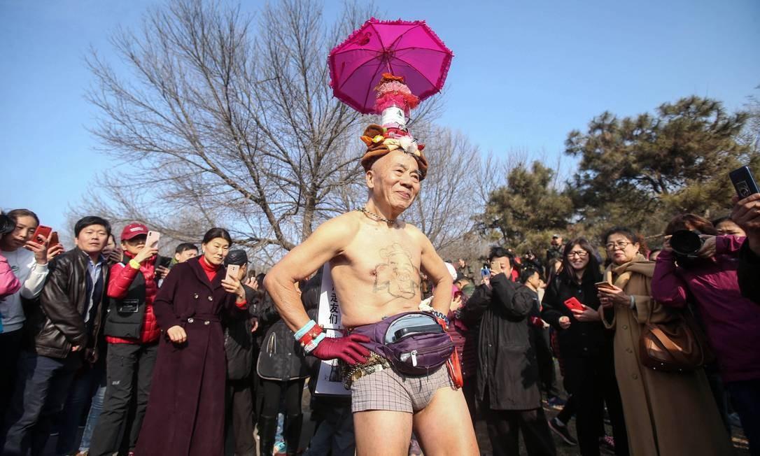 Fantasiado, um homem participa da corrida anual no Parque Olímpico da Floresta, em Pequim Foto: STR / AFP