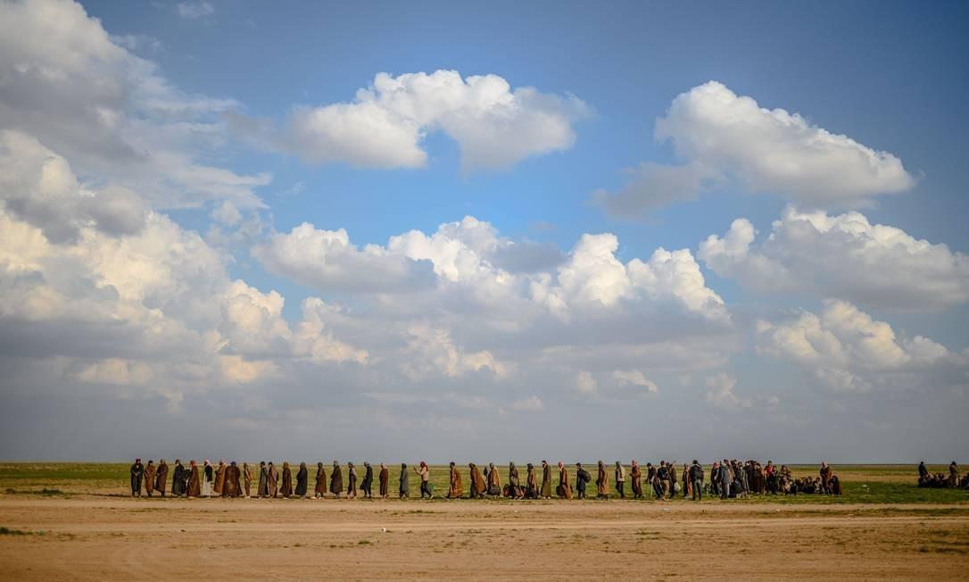 Grupos do norte da Síria fazem uma longa caminhada em direção a uma área controlada por combatentes das Forças Democráticas da Síria, que têm o apoio dos EUA Foto: BULENT KILIC / AFP