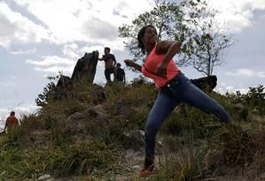 Manifestante lança pedra contra militares venezuelanos de Pacaraima, em Roraima Foto: RICARDO MORAES / REUTERS