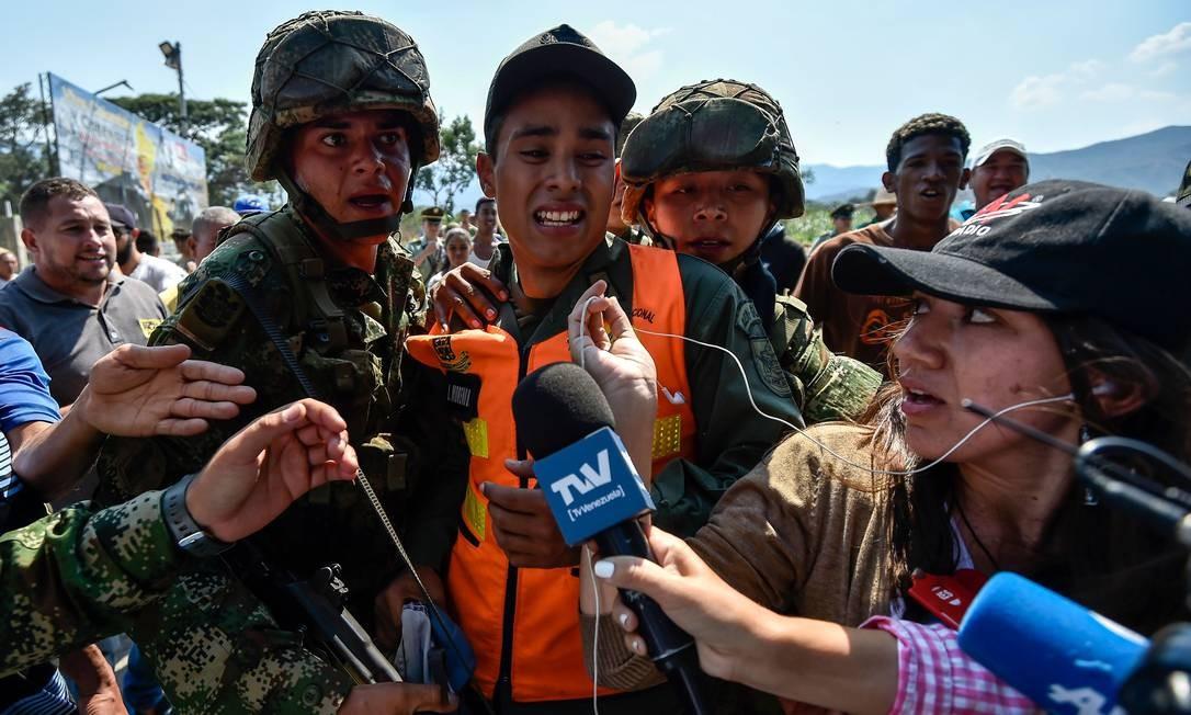 Soldados colombianos escoltam membro das Forças Armadas que desertou para a Colômbia Foto: LUIS ROBAYO / AFP