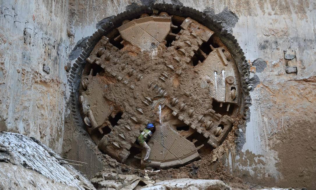 Operário indiano trabalha em meio à hélice de um perfuradora na construção de um túnel para linha de metrô, em Ahmedabad, na Índia Foto: SAM PANTHAKY / AFP