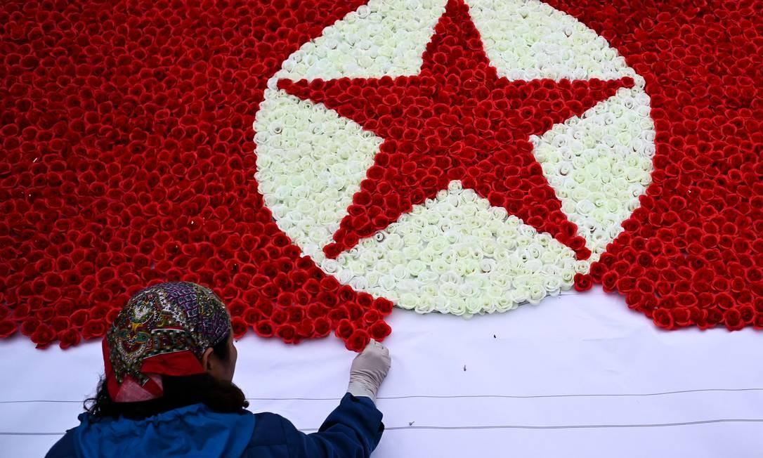 Um trabalhador constrói uma bandeira norte-coreana com flores de papel em uma rua, em Hanói, onde o presidente dos EUA, Donald Trump, e o líder norte-coreano, Kim Jong Un, encontram-se esta semana para a segunda cúpula EUA-Coréia do Norte Foto: JEWEL SAMAD / AFP