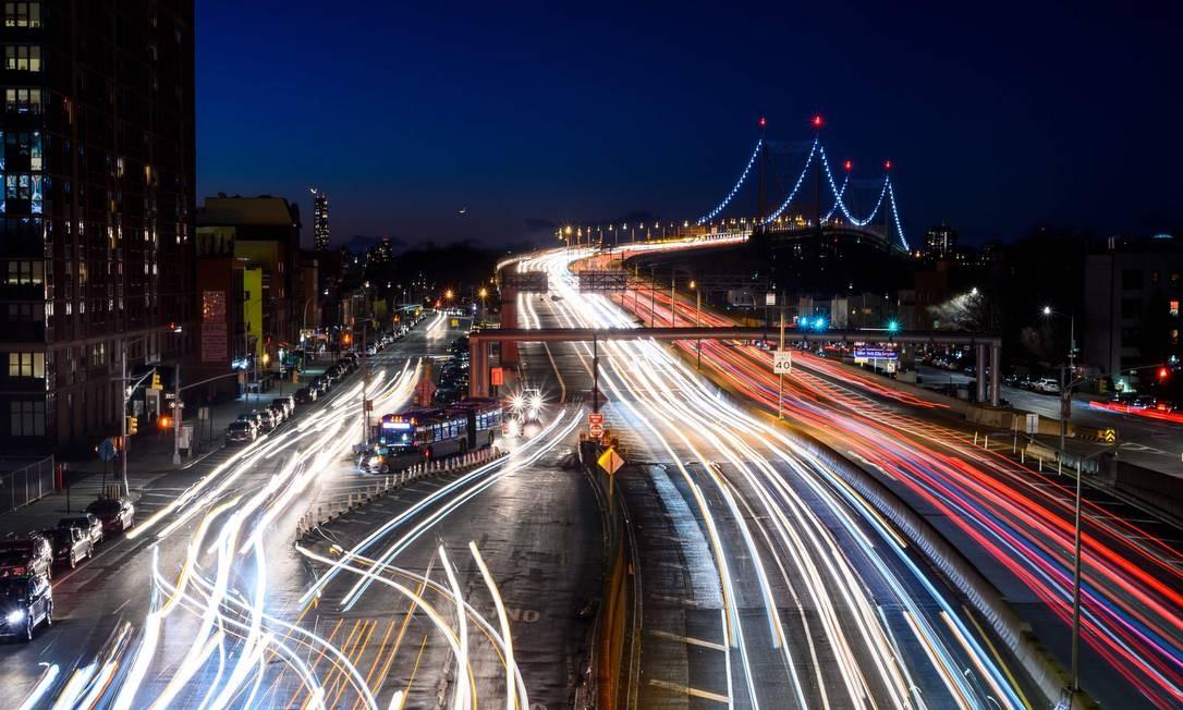 Imagem mostra rastros de luz deixados por carros que passaram pela East River, na Ponte Robert F. Kennedy, que leva até o Queens, em Nova York Foto: JOHANNES EISELE / AFP