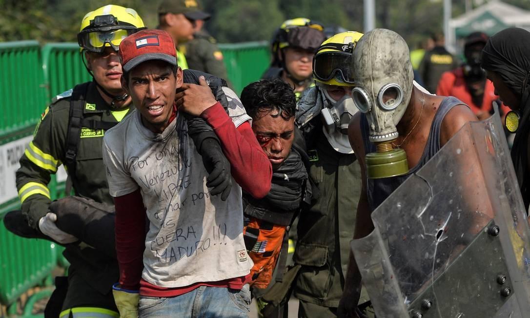 Um manifestante é auxiliado na Ponte Internacional Simon Bolívar, em Cúcuta, na Colômbia, após ser ferido em confrontos com as forças de segurança venezuelanas Foto: LUIS ROBAYO / AFP