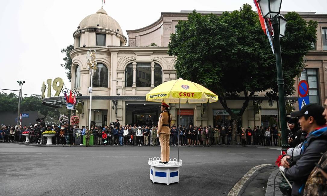 Uma policial vietnamita fica de guarda enquanto as pessoas se reúnem em torno de uma rua em Hanói para ver a comitiva de Kim Jong Un passar pelo local Foto: MANAN VATSYAYANA / AFP
