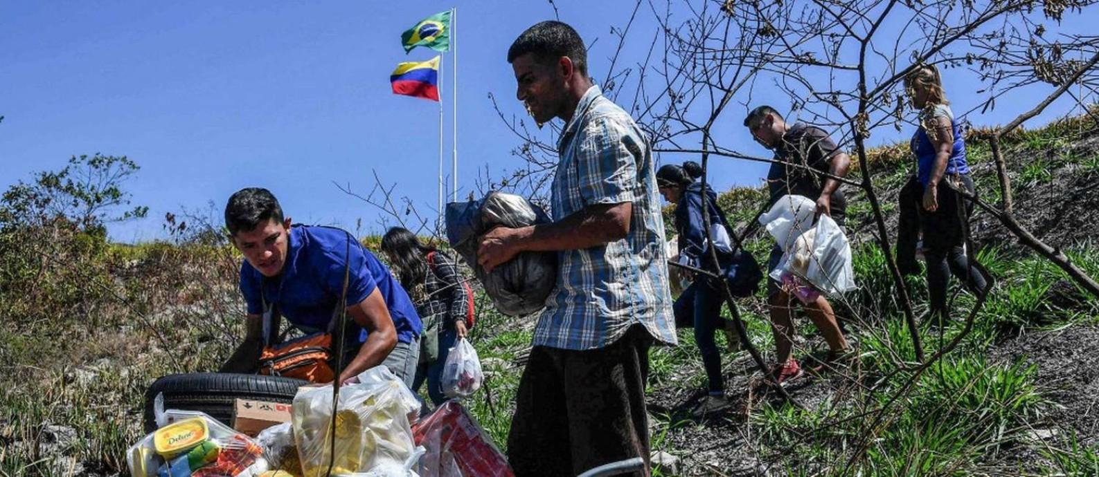 Venezuelanos enchem carrinho de mão com alimentos em Pacaraima para levar de volta ao país: rotas alternativas com a fronteira fechada Foto: NELSON ALMEIDA / AFP