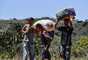 Venezuelanos cruzam fronteira com o Brasil levando mantimentos Foto: Nelson Almeida / AFP