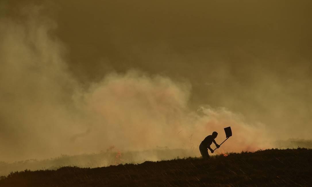 Bombeiros enfrentam um incêndio no pântano acima de Marsden, no noroeste da Inglaterra Foto: OLI SCARFF / AFP