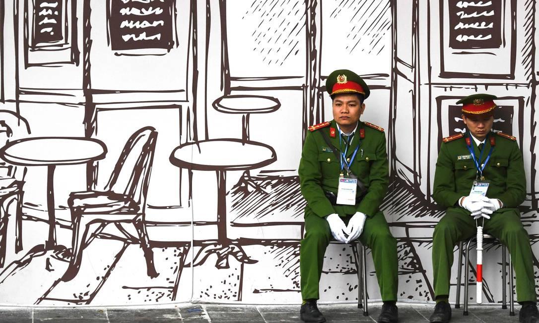 Policiais vietnamitas sentam-se em banquetas perto do hotel Sofitel Legend Metropole, em Hanói, onde acontece a segunda cúpula EUA-Coreia do Norte, com encontro entre o presidente dos EUA, Donald Trump, e do líder norte-coreano, Kim Jong-un Foto: YE AUNG THU / AFP