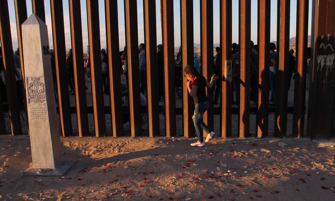 Uma menina de Anapra, um bairro nos arredores de Ciudad Juarez, no México, caminha rente a cerca da fronteira durante uma oração com padres e bispos do México e dos Estados Unidos Foto: HERIKA MARTINEZ / AFP