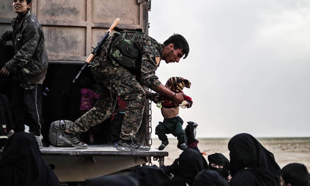 Combatente das Forças Democráticas da Síria (SDF), apoiada pelos EUA, ajuda civis em uma área de proteção para evacuados de Baghouz, na província de Deir Ezzor, onde extremistas do grupo Estado Islâmico se encontram entrincherados Foto: DELIL SOULEIMAN / AFP