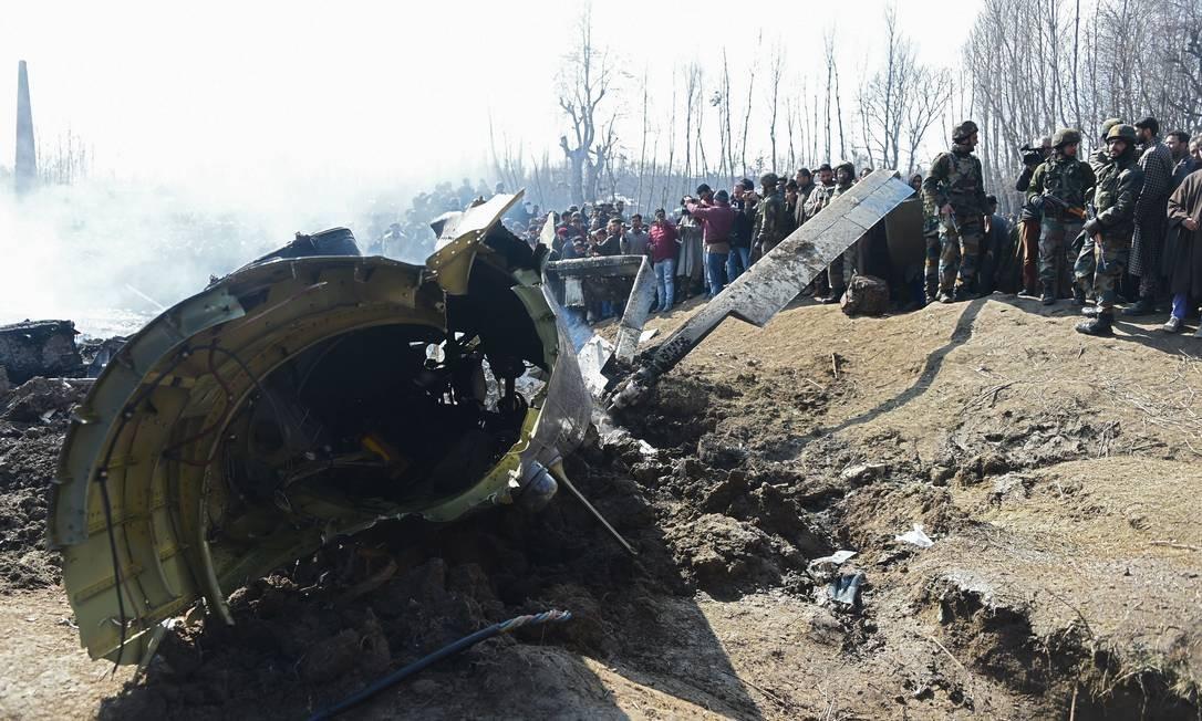 Soldados indianos observam destroços de um dos dois helicóptero da Força Aérea indiana que foram abatidos pelo Exército do Paquistão na manhã desta quarta-feira (27), na região da Caxemira Foto: TAUSEEF MUSTAFA / AFP