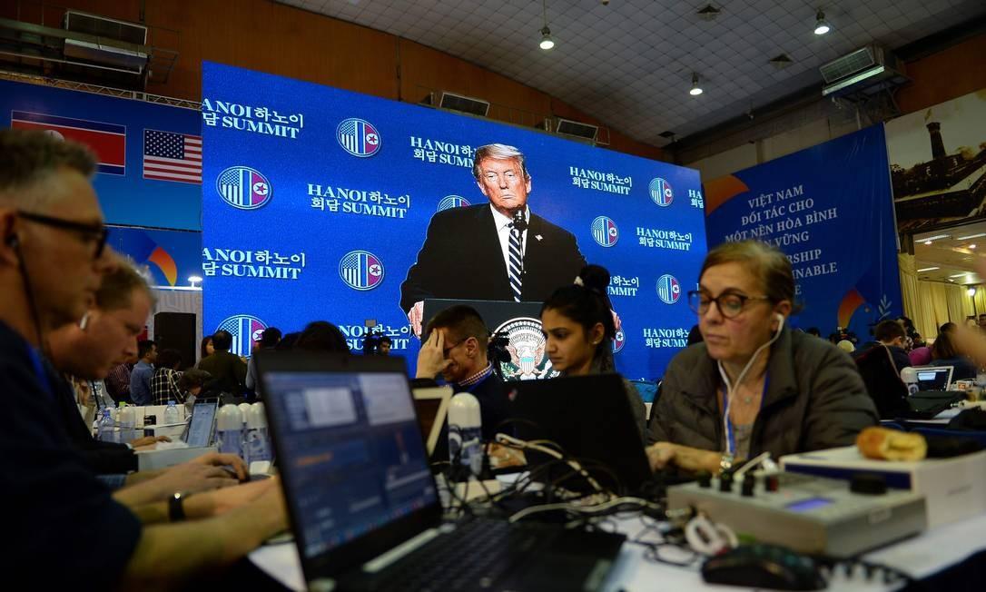 Jornalistas trabalham em um centro de mídia enquanto assistem à coletiva de imprensa do presidente dos EUA, Donald Trump. Cúpula terminou sem um acordo Foto: NHAC NGUYEN / AFP