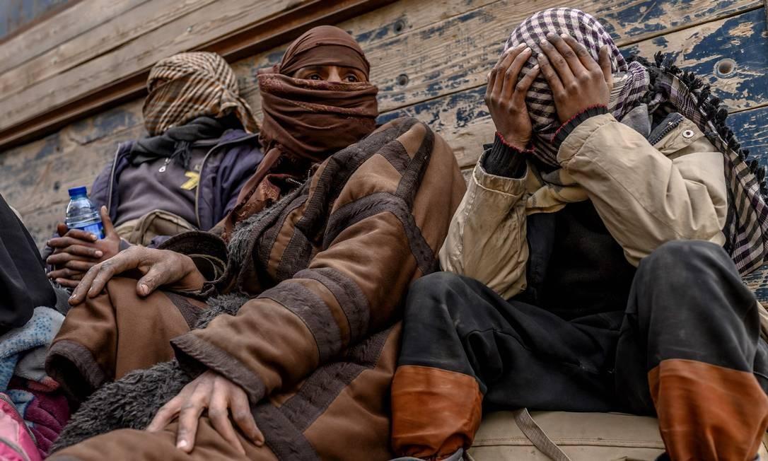 Homens suspeitos de serem do Estado Islâmico esperam pela revista dos membros das Forças Democráticas Sírias (SDF), lideradas por curdos e que contam com o apoio dos Estados Unidos Foto: DELIL SOULEIMAN / AFP