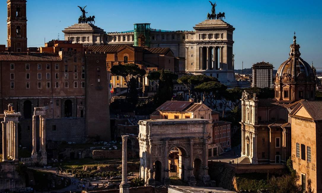 No Fórum Romano, monumentos de diversas épocas da cidade convivem em harmonia, como a Igreja de São Lucas e Santa Martina (à direita), o Arco de Sétimo Severo (centro), o Capitólio (esquerda) e o Altar da Pátria (no fundo) Foto: LAURENT EMMANUEL / AFP
