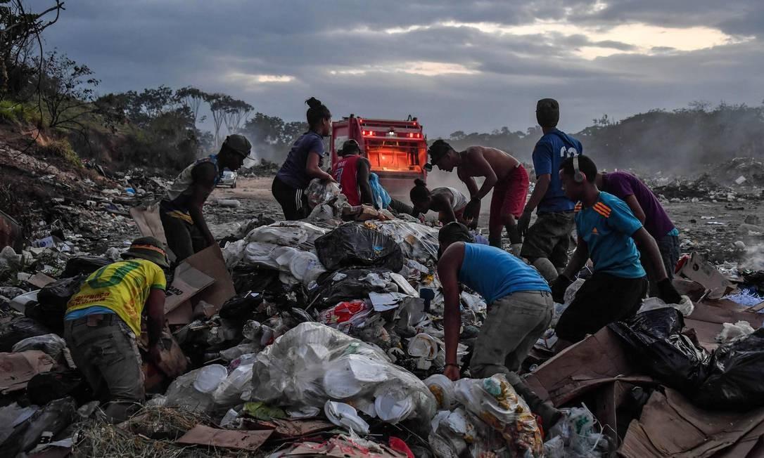Catadores venezuelanos vasculham o lixo em um aterro sanitário em Pacaraima, em Roraima, na fronteira do Brasil com a Venezuela Foto: NELSON ALMEIDA / AFP