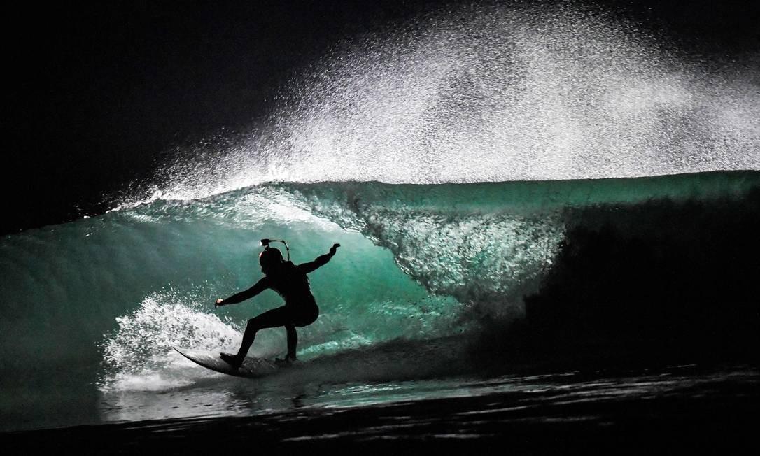 Um homem surfa à noite usando um farol poderoso à prova d'água na praia de Cap Frehel, em Plevenon, Grã-Bretanha, no final de 27 de fevereiro de 2019 Foto: LOIC VENANCE / AFP