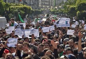 """Argelinos marcham segurando cartazes em árabe com os dizeres """"pacífico"""" e """"sair quer dizer"""" em protesto nesta sexta-feira na capital Argel: velho e doente, presidente há 20 anos no poder quer concorrer a um quinto mandato Foto: AFP/RYAD KRAMDI"""