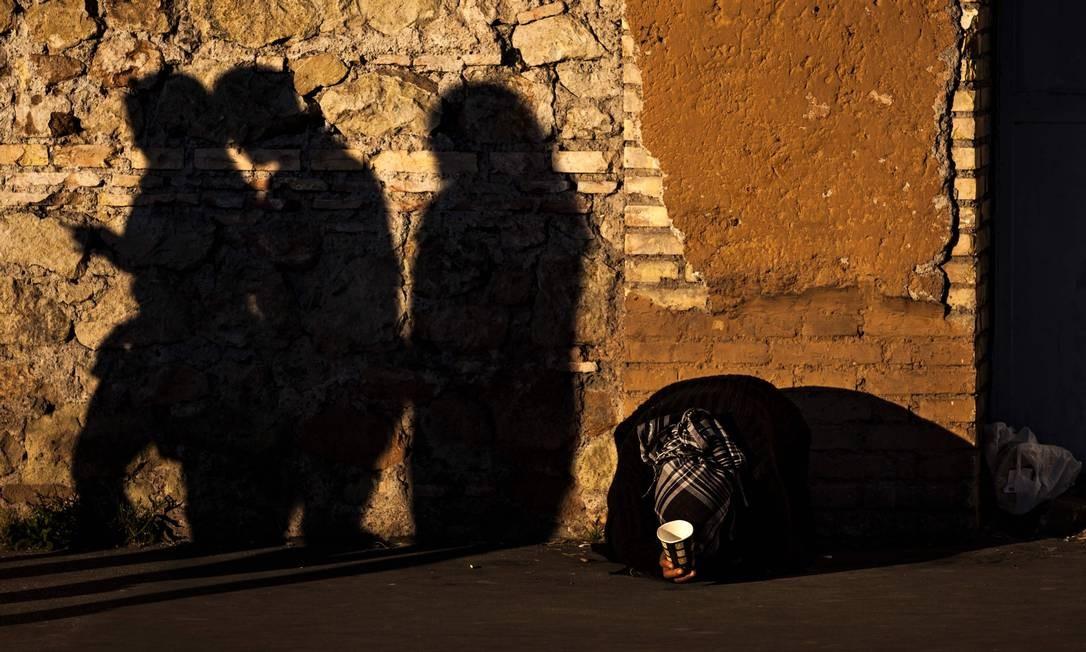 Sombras projetadas na parede de pessoas que passam próximo a uma moradora de rua em Roma, na Itália Foto: LAURENT EMMANUEL / AFP