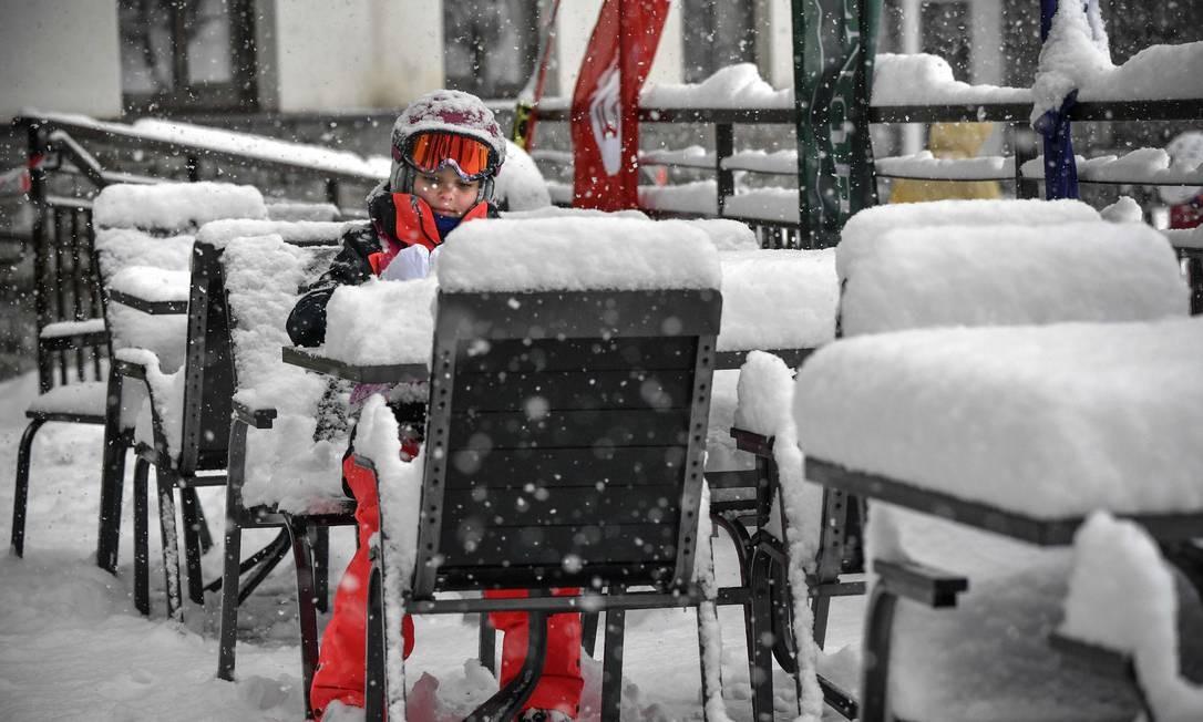 Uma menina senta-se a uma mesa de uma cafeteria durante a forte nevasca no resort Rosa Khutor, fora de Sótchi, na Rússia Foto: ALEXANDER NEMENOV / AFP