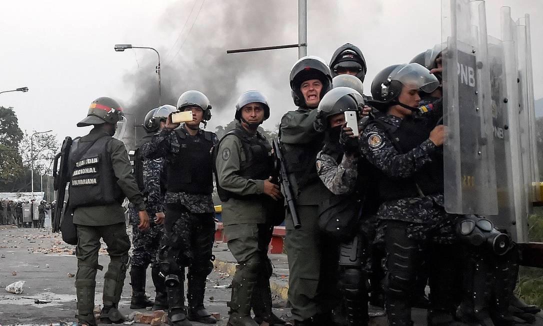 Forças de segurança da Venezuela filmam confrontos com opositores em celulares em ponte na fronteira com a Colômbia Foto: RAUL ARBOLEDA / AFP/25-02-2019