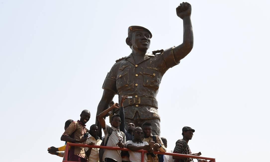 Moradores posam sob a estátua de bronze do ex-presidente Thomas Sankara, de Burkina Faso, morto em 15 de outubro de 1987, à margem da inauguração de seu memorial, no Conseil de l'Entente, em Ouagadougou Foto: ISSOUF SANOGO / AFP