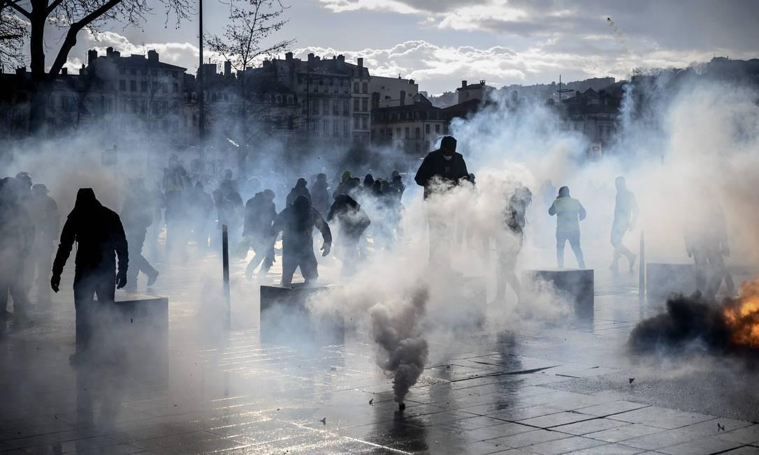 Os manifestantes tentam se proteger do gás lacrimogêneo durante uma manifestação antigovernamental convocada pelo movimento Coletes Amarelos, em Lyon, no centro-leste da França Foto: JEAN-PHILIPPE KSIAZEK / AFP