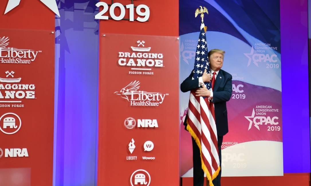 O presidente dos EUA, Donald Trump, abraça a bandeira dos EUA em su chegada para falar na Conferência de Ação Política Conservadora (CPAC) em National Harbor, Maryland Foto: NICHOLAS KAMM / AFP