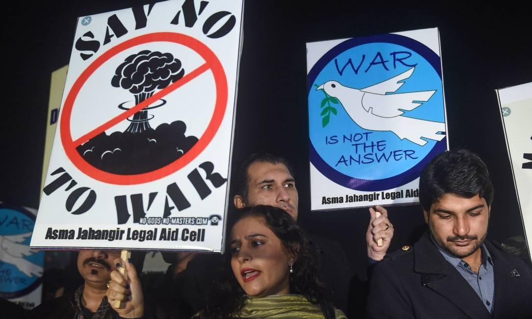 """Pessoas mantêm cartazes dizendo """"Diga não à guerra"""" e """"A guerra não é a resposta"""" durante uma vigília pela paz em Lahore. Tensões entre a Índia e o Paquistão devastaram o dia 2 de março. Sete pessoas dos dois lados da fronteira ferozmente disputada de Caxemira morreram. As tensões aumentaram desde que um atentado suicida na Caxemira, no mês passado, afirmou que militantes do Paquistão mataram 40 paramilitares indianos Foto: ARIF ALI / AFP"""