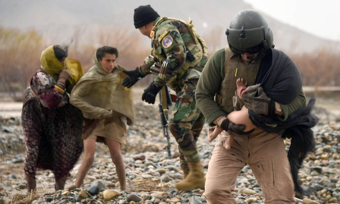 Nesta foto tirada em 2 de março de 2019, um membro da tripulação da Força Aérea afegã (R) carrega uma criança durante uma operação de evacuação em uma área afetada pelas inundações do distrito de Arghandab, na província de Kandahar. - Pelo menos 20 pessoas foram mortas por enchentes na província de Kandahar, no sul do Afeganistão, informou a ONU em 2 de março de 2019, quando fortes chuvas varreram casas e veículos e potencialmente danificaram milhares de casas. Foto: JAVED TANVEER / AFP