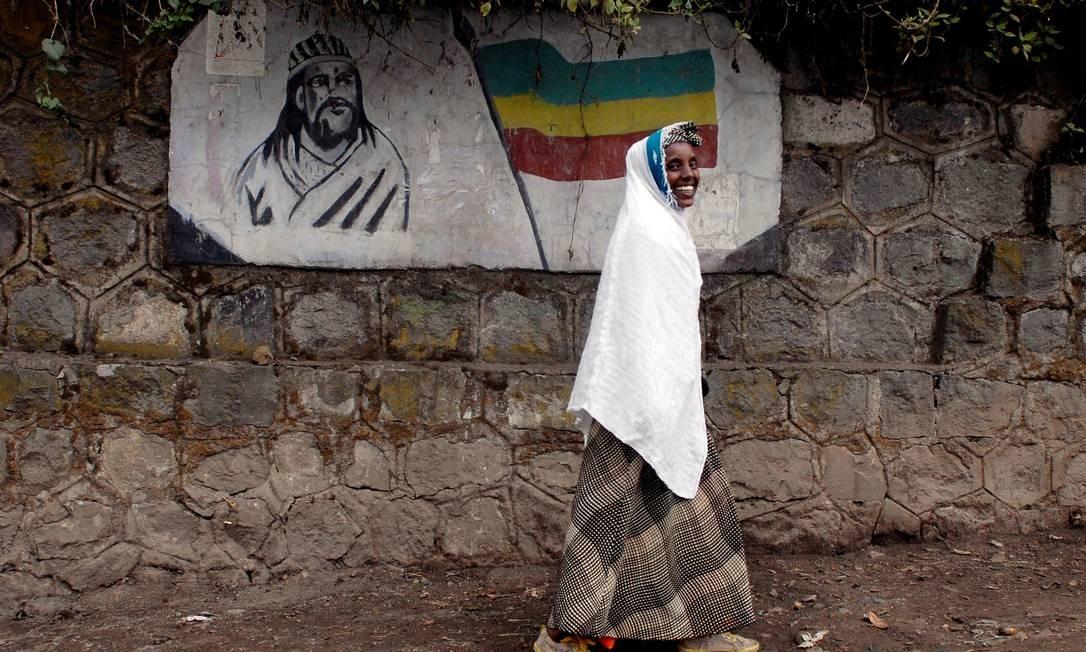 Mulher etíope passa por um mural que retrata o imperador Tewodros II da Etiópia, em Adis Abeba. Foto de 01-06-2007 Foto: Andrew Heavens / REUTERS