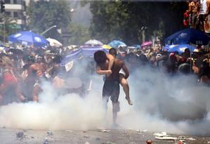Folião carrega uma mulher que passou mal por causa do gás lacrimogêneo no bloco da Ludmilla Foto: Guilherme Pinto / Agência O Globo
