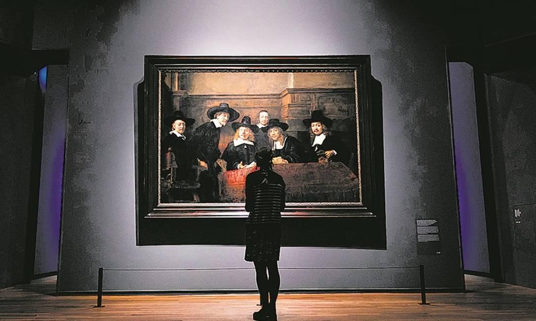 """Mulher observa """"Os síndicos da guilda dos fabricantes de tecidos"""", obra da exposição """"All the Rembrandts"""", do Rikksmuseum (Holanda), dedicada ao mestre holandês Foto: Remko de Waal / AFP"""
